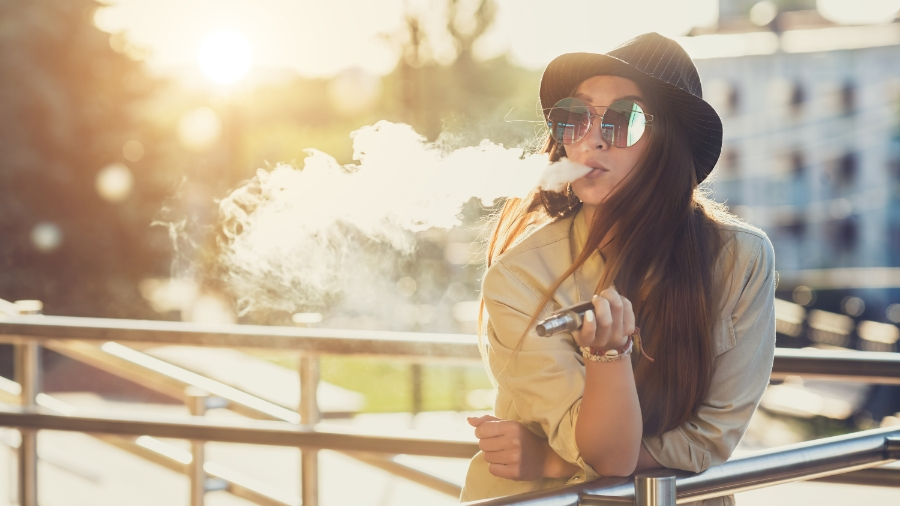 young woman smoking from a vaporizer