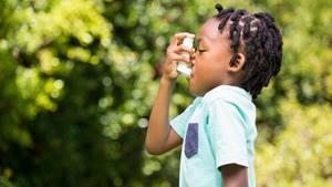 Boy using inhaler in park