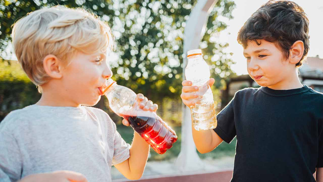Two young boys drinking beverages