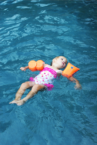 Young girl floating in pool