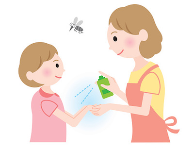 Mom spraying insect repellent on daughter