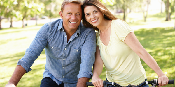Mature couple riding bicycles in the park 176993897_3869x2579