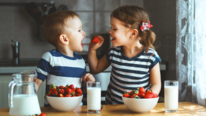 Children share a bowl of strawberries