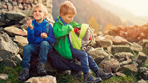 Boys eat snack while hiking